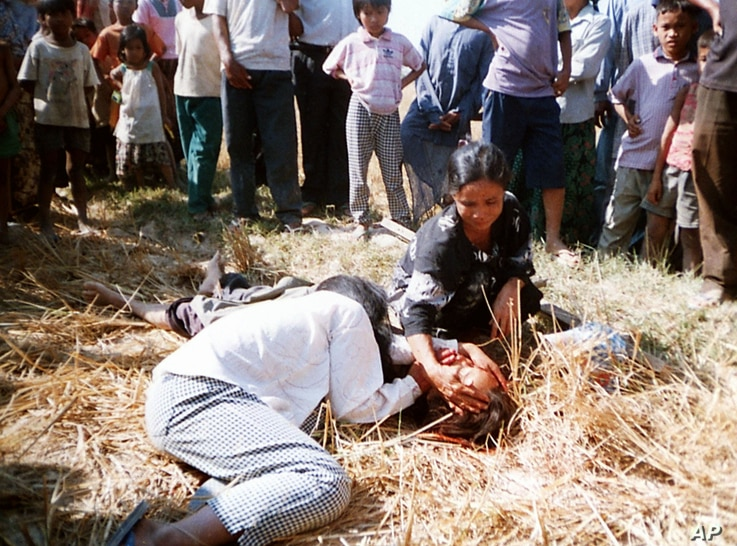 FILE - An unidentified suspected thief lies dead on the ground as his relatives grieve over his body in the midst of a mob that had beaten him to death, in a southern district of Phnom Penh, Cambodia, April 11, 2002.
