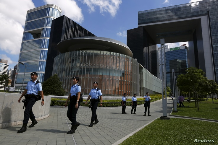 FILE - Policemen patrol at the park in front of Legislative Council (C) and government headquarters (R) in Hong Kong, China.