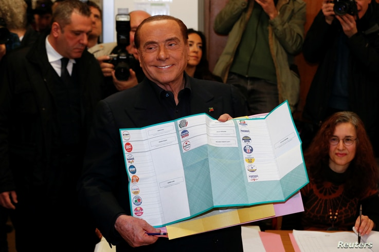 Forza Italia party leader Silvio Berlusconi holds his ballot as he prepares to cast his vote at a polling station in in Milan, Italy, March 4, 2018.