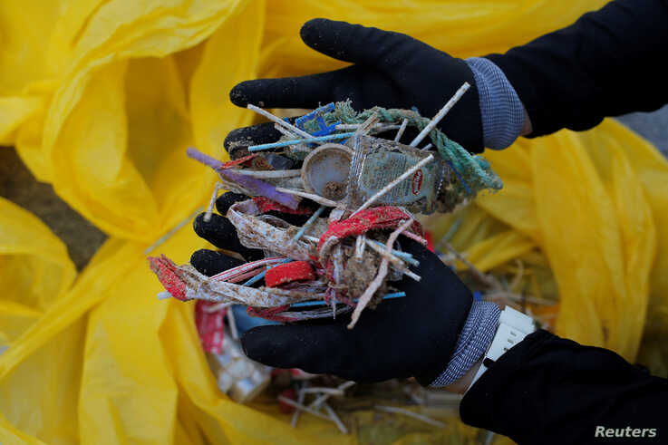 FILE - A volunteer shows plastics retrieved from the ocean, after a garbage collection, ahead of World Environment Day, on La Costilla Beach, on the coast of the Atlantic Ocean in Rota, Spain, June 2, 2018.