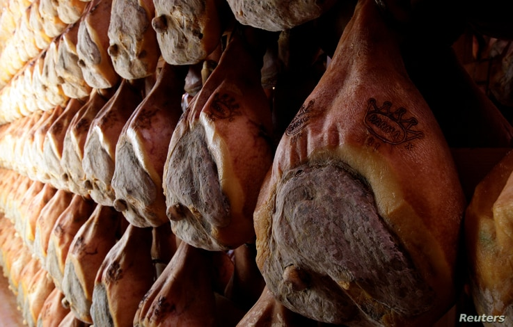 FILE - Lines of Parma hams are hung to dry in a special room in Langhirano near Parma, Italy, Oct. 13, 2009.