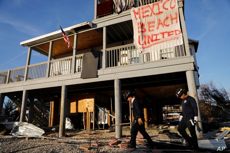 A banner hangs from a damaged home as a South Florida urban search and rescue team checks for survivors of Hurricane Michael, in Mexico Beach, Florida, Oct. 12, 2018.