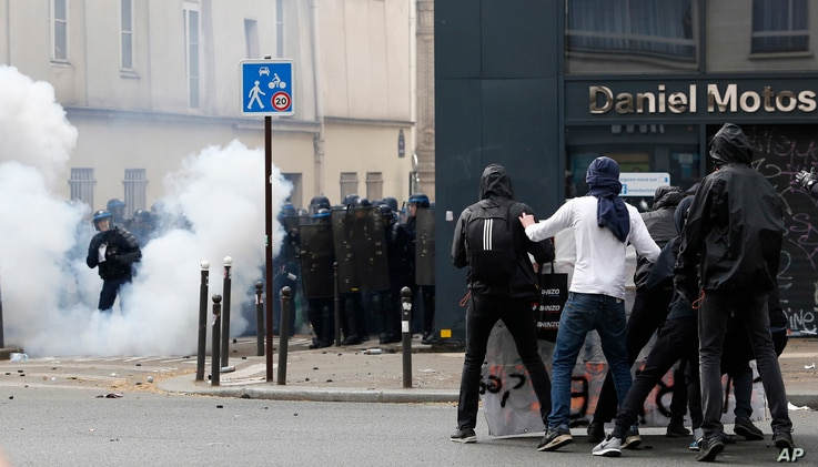 Youth, right, face French riot police officers during the May Day demonstration, May 1, 2017, in Paris. Paris police are firing tear gas at rowdy protesters on sidelines of May Day workers' march.