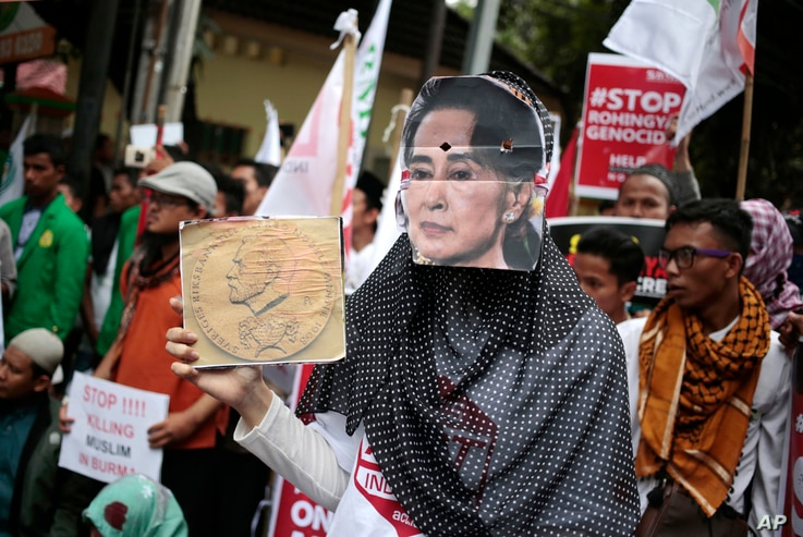 A Muslim woman wears a mask of Myanmar's Aung San Suu Kyi during a rally against the persecution of Rohingya Muslims, outside the embassy of Myanmar in Jakarta, Indonesia, Nov. 25, 2016.
