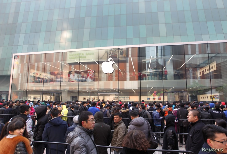 FILE - Customers wait for the opening of an Apple store in Shenyang, Liaoning province, Feb. 28, 2015.