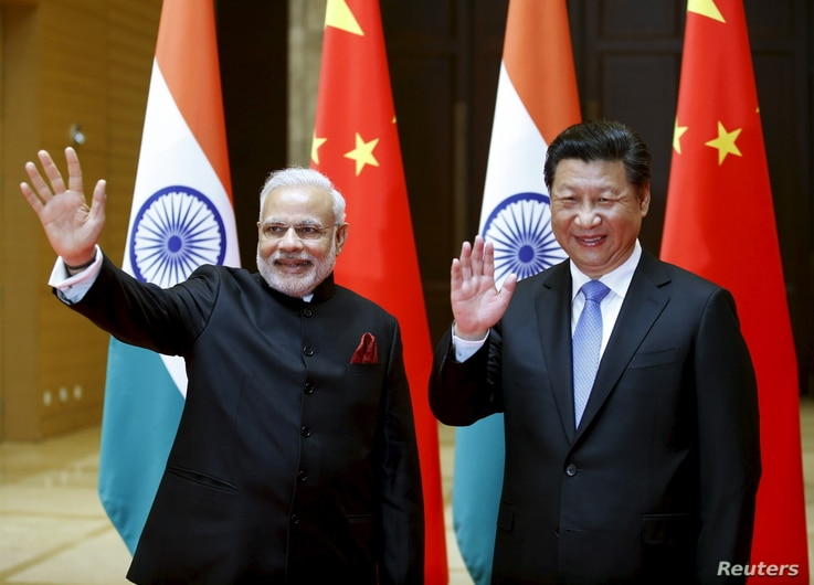 Indian Prime Minister Narendra Modi (L) and Chinese President Xi Jinping wave to journalists before they hold a meeting in Xian, Shaanxi province, China, May 14, 2015.