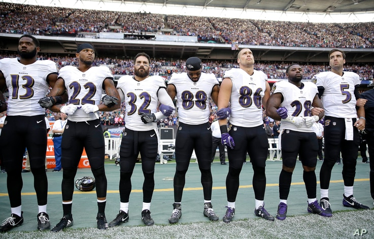 Baltimore Ravens players link arms during the playing of the U.S. national anthem before an NFL football game against the Jacksonville Jaguars at Wembley Stadium in London, Britain, Sept. 24, 2017.