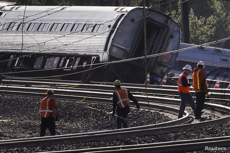 Officials survey the site of a derailed Amtrak train in Philadelphia, Pennsylvania May 13, 2015. An Amtrak passenger train with more than 200 passengers on board derailed in north Philadelphia on Tuesday night, killing at least five people and injuri...