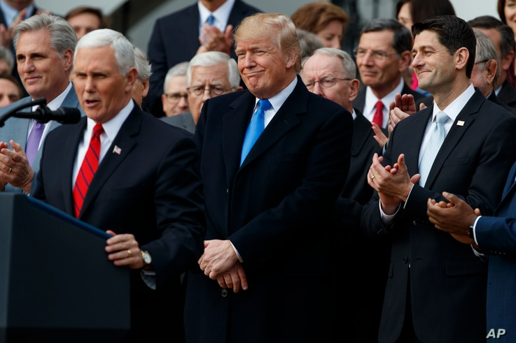 President Donald Trump smiles as Vice President Mike Pence speaks during an event on the South Lawn of the White House in Washington, Dec. 20, 2017, to acknowledge the final passage of tax overhaul legislation by Congress.