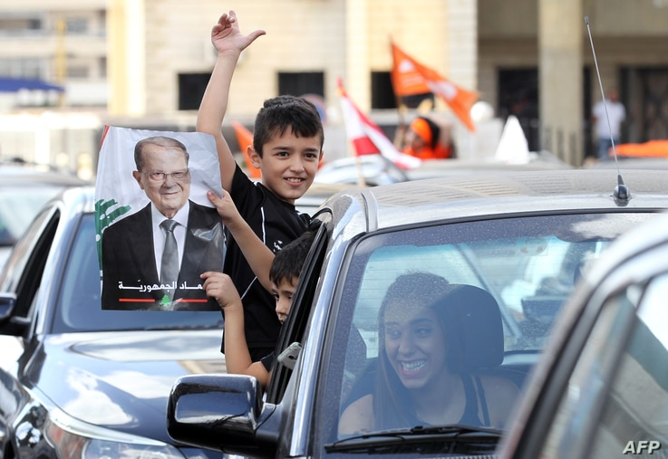 Lebanese people take to the streets in Jdeideh, on the northern outskirts of the capital Beirut, to celebrate the election of former general Michel Aoun (portrait) as president, Oct. 31, 2016.