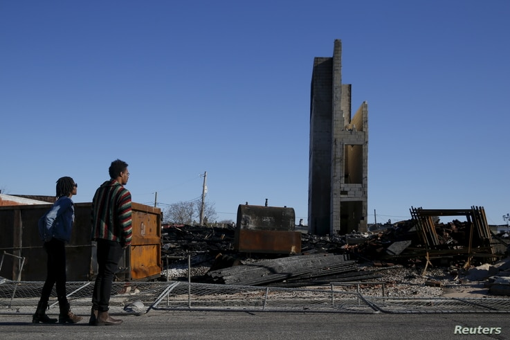 People stand outside the burned community center and apartments across the street from the Southern Baptist Church in Baltimore, Maryland April 28, 2015.