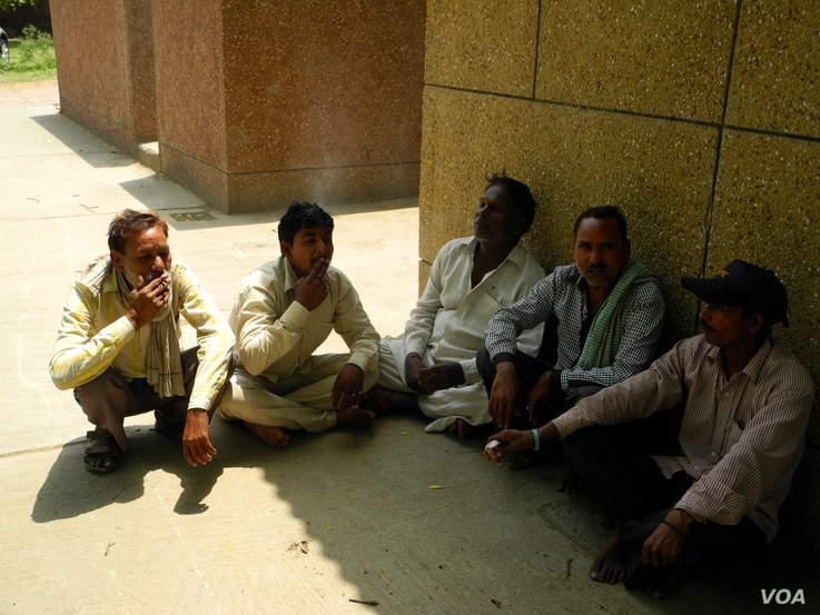 A group of workers relax and smoke during a midday break. (A. Pasricha/VOA)