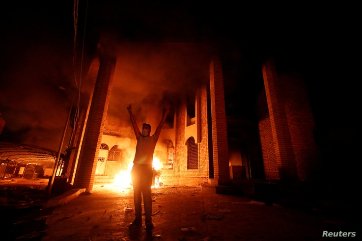 FILE - An Iraqi protester gestures in front of the burned Iranian consulate in Basra, Iraq, Sept. 7, 2018.