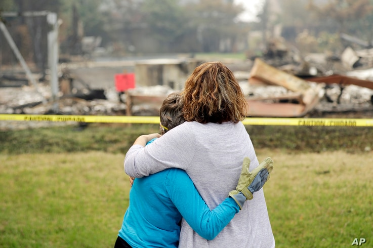 Carol Smith, left, gets a hug from her daughter Suzie Scatena, after seeing her fire-ravaged home for the first time, Aug. 2, 2018, in Redding, Calif.