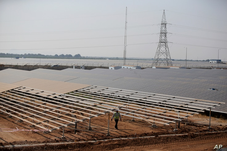 An official walks past solar panels at the Pavagada Solar Park 175 kilometers (109 miles) north of Bangalore, India, March 1, 2018. The park is expected to produce 2,000 megawatts of power according to a press release.