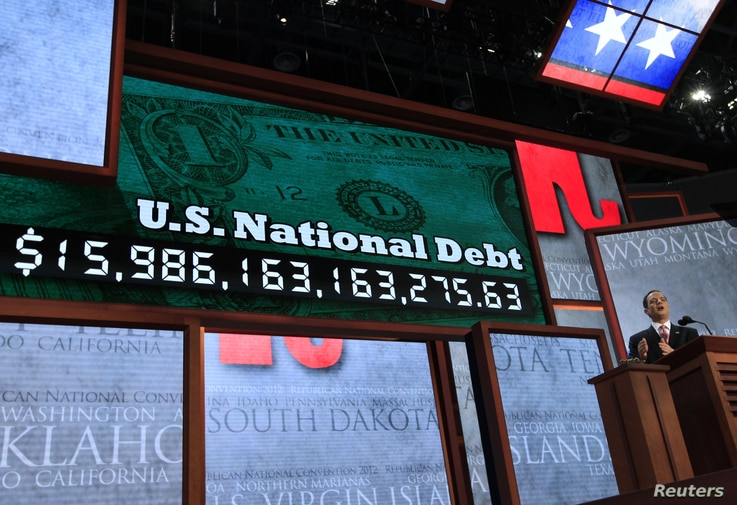 Standing in front of a large U.S. national debt clock, Republican National Committee Chairman Reince Priebus addresses the 2012 Republican National Convention opening session in Tampa, Florida, August 27, 2012.