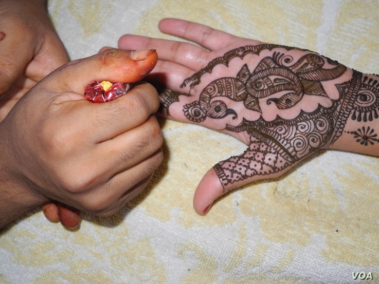 Putting henna on brides and guests is one of the elaborate ceremonies at Indian weddings. (A. Pasricha/VOA)