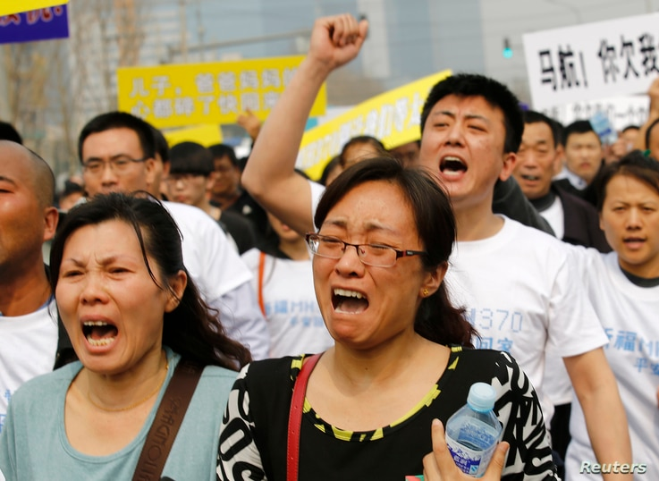 Family members of passengers on board Malaysia Airlines MH370 shout slogans during a protest in front of the Malaysian embassy in Beijing, March 25, 2014.