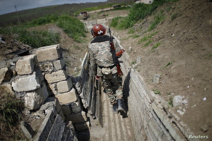 FILE - Ethnic Armenian soldiers walk in a trench at their position near Nagorno-Karabakh's boundary, April 8, 2016.