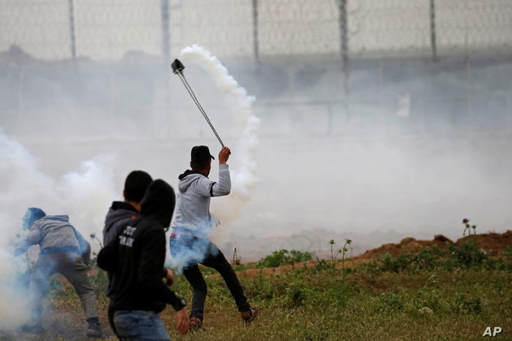 A Palestinian demonstrator uses a sling to hurl back a tear gas canister fired by Israeli forces during a protest marking Land Day and the first anniversary of a surge of border protests, at the Israel-Gaza border fence east of Gaza City, March 30, 2...