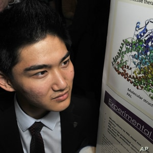 Jack Li poses with his poster board, which explains his research on a therapy for a rare genetic disease.