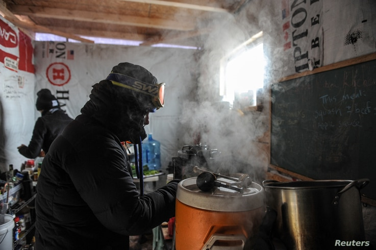 """A woman makes coffee in a kitchen in the Oceti Sakowin camp as """"water protectors"""" continue to demonstrate against plans to pass the Dakota Access pipeline near the Standing Rock Sioux Reservation, near Cannon Ball, N.D., Dec. 6, 2016."""