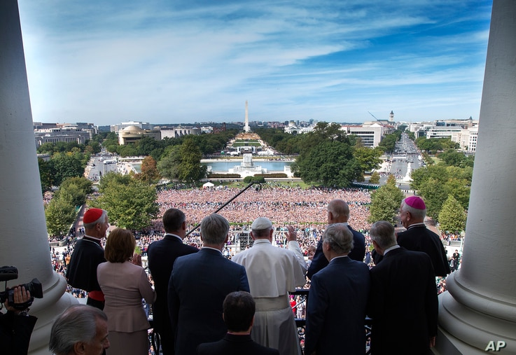 Pope Francis, accompanied by members of Congress, waves to the crowd from the Speakers Balcony on Capitol Hill in Washington, Sept. 24, 2015, after addressing a joint meeting of Congress inside.