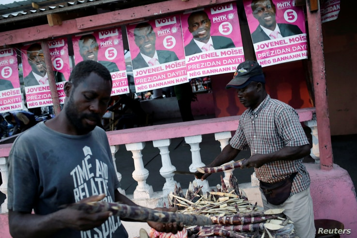 A customer checks sugar cane sold by a street vendor next to posters of presidential candidate Jovenel Moise of PHTK (Bald Head Haitian Party) before the election in a street of Les Cayes, Haiti, Nov. 19, 2016.