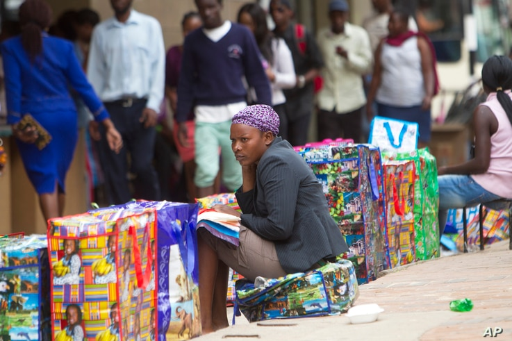 FILE - A bag vendor waits for clients on a street in Harare, Zimbabwe, Dec. 20, 2016. Many people in this once-prosperous southern African country are struggling to make ends meet as the economy implodes.