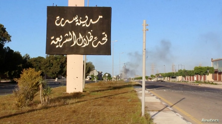 "A sign which reads in Arabic, ""The city of Sirte, under the shadow of Sharia"" is seen as smoke rises in the background while forces aligned with Libya's new unity government advance on the eastern and southern outskirts of the Islamic State stronghol..."