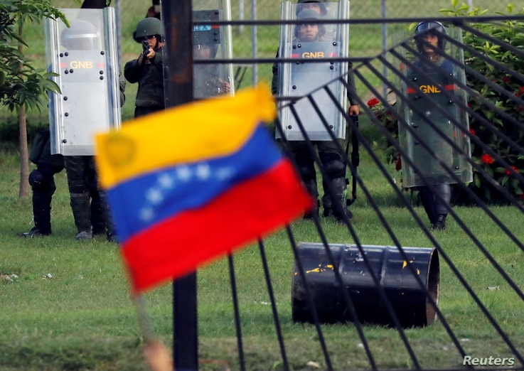 A member of the riot security forces points a gun at an opposition supporter holding a Venezuelan national flag during clashes at a rally against Venezuelan President Nicolas Maduro's government in Caracas, June 22, 2017.