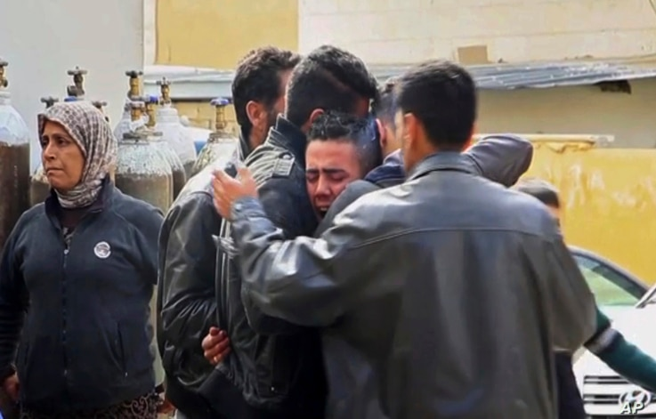 Men grieve outside a hospital following Turkish airstrikes on the Syrian Kurdish enclave of Afrin, northwestern Syria, Feb. 14, 2018. Nearly a month into Turkey's offensive in Afrin, hundreds of thousands of Syrians are hiding from bombs and airstrik...