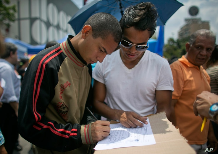 A man signs a petition to initiate a recall referendum against Venezuela's President Nicolas Maduro in Caracas, April 27, 2016.