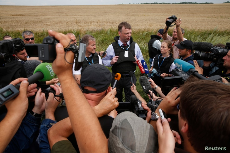 FILE - An OSCE monitor speaks to journalists near Grabovo in Ukraine's eastern Donetsk region July 19, 2014. Coverage of the conflict in eastern Ukraine between government forces and pro-Russia separatists has been a delicate task for many Ukrainian ...