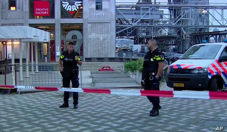 In this image taken from video, officers stand behind a cordoned-off area in Rotterdam, Aug. 23, 2017, after a concert by an American band was cancelled following a threat.