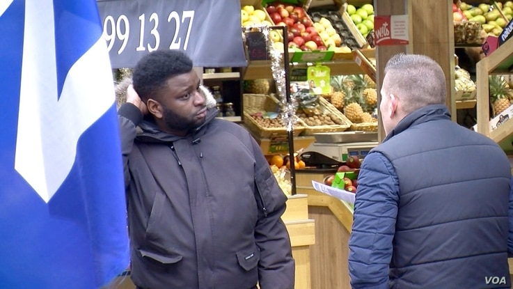 City Councillor Laurent Salles talks to a Suresnes resident who says he's fed up with the political system. Salles counters critics who claim the FN is racist. (L. Bryant/VOA)