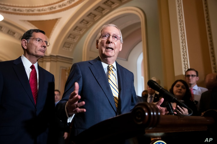 Senate Majority Leader Mitch McConnell, R-Ky., joined at left by Sen. John Barrasso, R-Wyo., speaks to reporters about the political battle for confirmation of President Donald Trump's Supreme Court nominee, Brett Kavanaugh, following a closed-door G...
