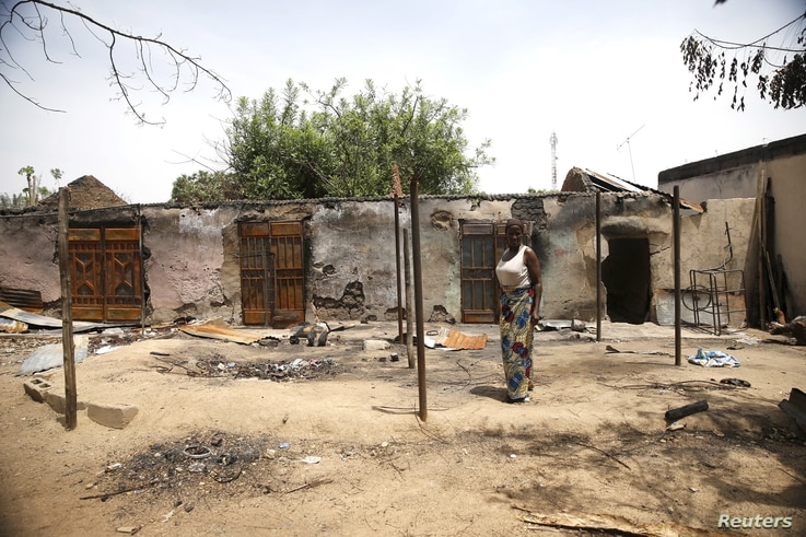 A woman stands in front of a burnt building in Michika town, after the Nigerian military recaptured it from Boko Haram, in Adamawa state, May 10, 2015.