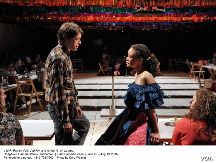 """Patrick Vaill as Jud Fry and Amber Gray as Laurey perform in Gideon Lester's production of """"Oklahoma!,"""" which seeks to help the audience feel the musical's conflicting emotions by placing them close to the action — at long tables on all four side..."""