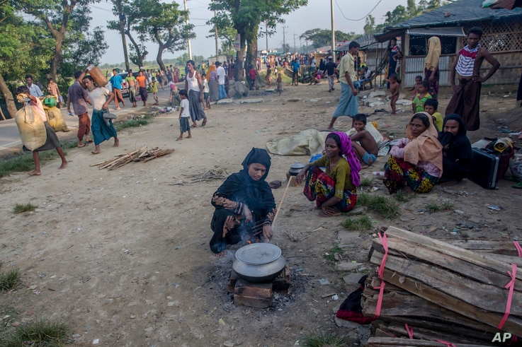 A Rohingya Muslim woman, who crossed over from Myanmar into Bangladesh, cooks food by the roadside near Mushani refugee camp, Bangladesh, Saturday, Sept. 16, 2017. United Nations agencies say an estimated 409,000 Rohingya Muslims have fled to Banglad...