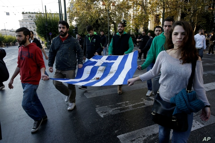 University students hold a blood-stained Greek flag from the deadly 1973 student uprising in Athens, Nov. 17, 2015. Thousands of people marched to commemorate a student uprising that was crushed by the country's military regime in 1973.