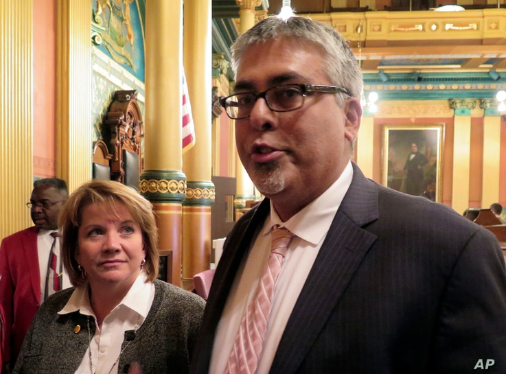 Rep. Sam Singh, D-East Lansing, right, speaks to reporters after being elected as the next House minority leader in Lansing, Mich., Nov. 10, 2016.  Rep. Christine Greig, D-Northville, left, who was chosen to be the minority floor leader, looks on.