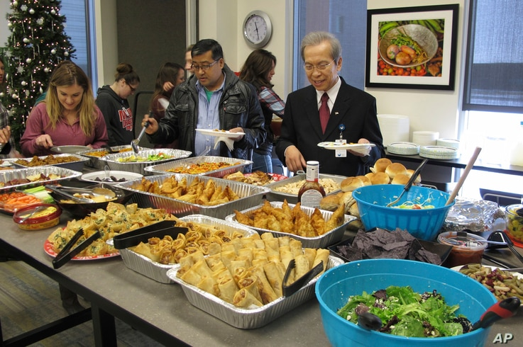 FILE - Tri Phan, right, begins the lunch line for his retirement party at Lutheran Social Services in Fargo, N.D., Dec. 15, 2017. Phan, 66, spent nearly three decades working in the agency's refugee resettlement program, helping thousands of immigran...