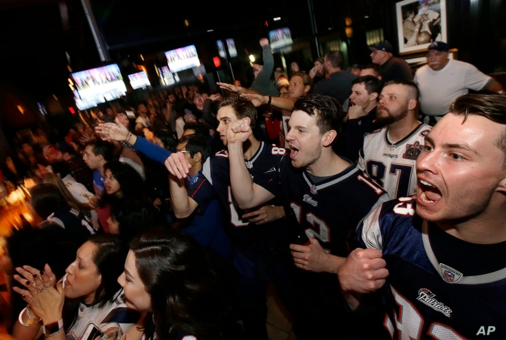 Coleman Hands, center, of Dallas, Davis Smith, second from right, of Austin, Texas, and Brian Moran, right, of Boston cheer while watching the first half of the NFL Super Bowl 52 football game between the New England Patriots and the Philadelphia Eag...