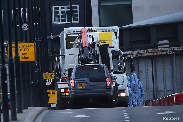 Forensics investigators work as a white van is carried away from London Bridge, after attackers rammed a hired van into pedestrians on London Bridge and stabbed others nearby killing and injuring people, in London, Britain June 4, 2017.
