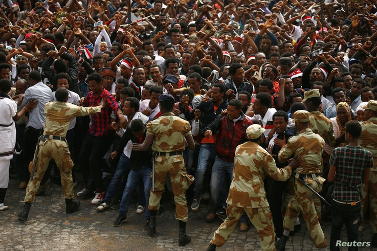 FILE - Demonstrators chant slogans while flashing the Oromo protest gesture during Irreecha, the thanksgiving festival of the Oromo people, in Bishoftu town, Oromia region, Ethiopia, Oct. 2, 2016.
