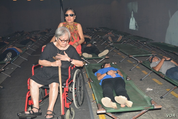 """Rosario """"Charito"""" Planas, political opponent of dictator Ferdinand Marcos and herself a detainee, passes through the """"Hall of Restless Sleep,"""" a dramatization of political detainees in captivity.  EDSA Revolution Experiential Museum, Quezon City, Feb..."""