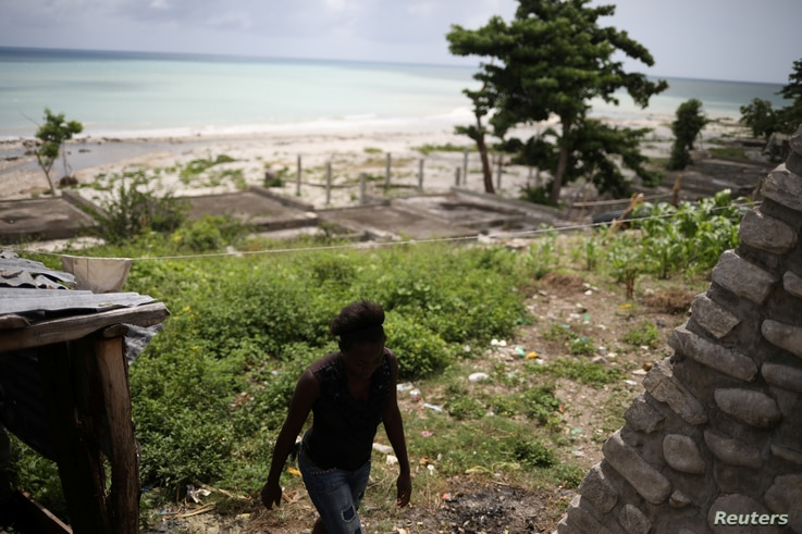 Myrlande Nazaire walks outside her residence in Port-Salut, Haiti, May 6, 2017. Myrlande says that one of her children was fathered by a U.N. peacekeeper. The paternity and child support issue is another awkward legacy of the 13-year U.N. mission, kn