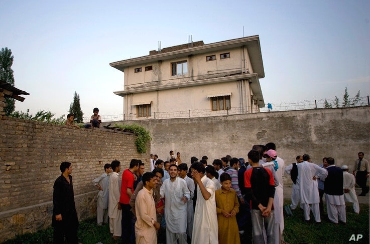 FILE - local residents gather outside a house in Abbottabad, Pakistan, where al-Qaida leader Osama bin Laden was killed in a raid the day before.