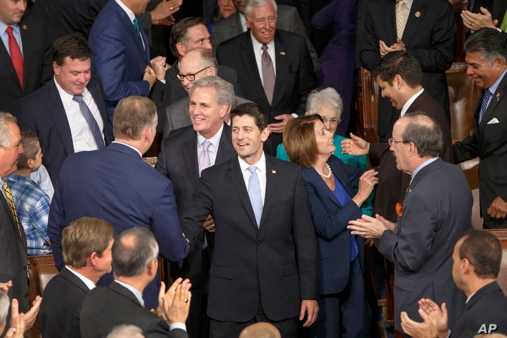 Newly-elected House Speaker Paul Ryan of Wis., escorted by House Minority Leader Nancy Pelosi of Calif., and House Majority Leader Kevin McCarthy of Calif., walks into the House Chamber on Capitol Hill in Washington, Oct. 29, 2015.